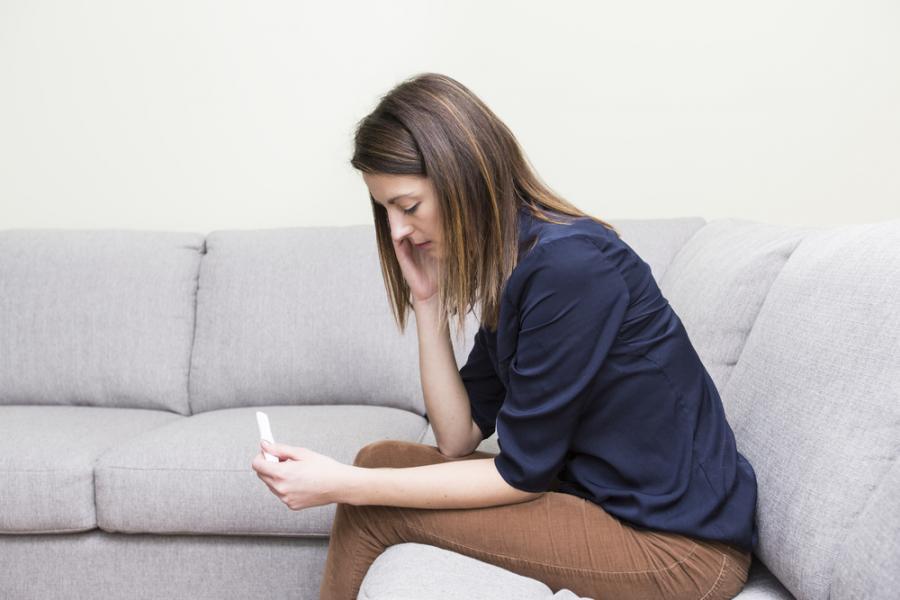 Kobieta patrzy na test ciążowy