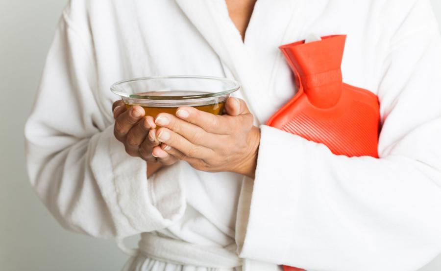 Kobieta trzyma herbatę i termofor