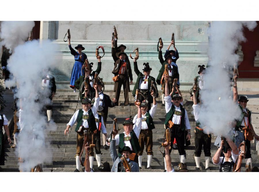 Mężczyźni ubrani w tradycyjne stroje oddają salwę oznajmiającą koniec Oktoberfest