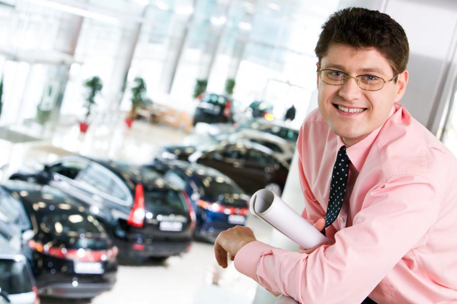 Zadowolony mężczyzna w salonie samochodowym