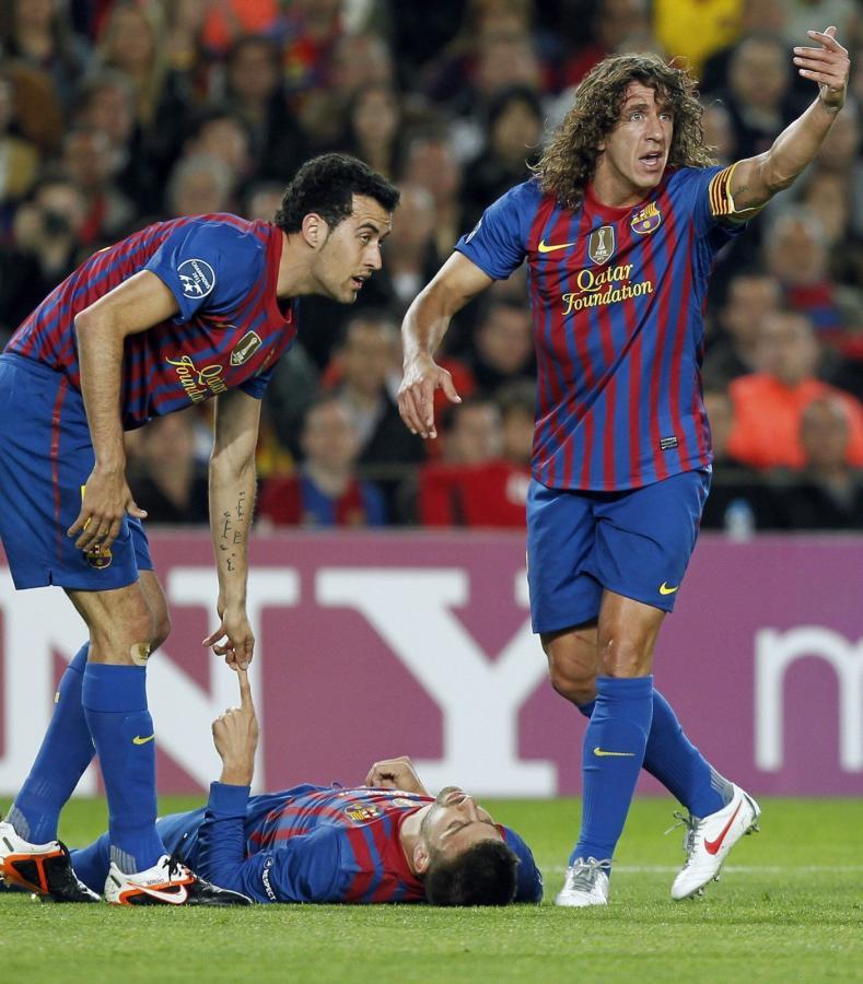 Gerard Pique dostał wstrząsy mózgu i leży na murawie. Obok stoją Carles Puyol i Segio Busquets