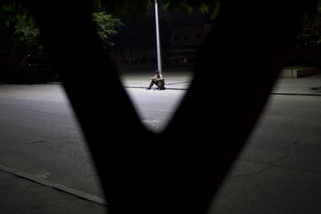 Mężczyzna czyta pod latarnią
