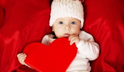 Niemowlę trzyma poduszkę-serce