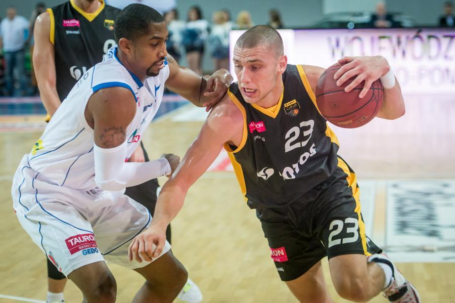 Szarżujący z piłką Michał Michalak (P) z Trefla Sopot mija blokującego Chase Simona (L) z miejscowego Anwilu w meczu ekstraklasy koszykarzy
