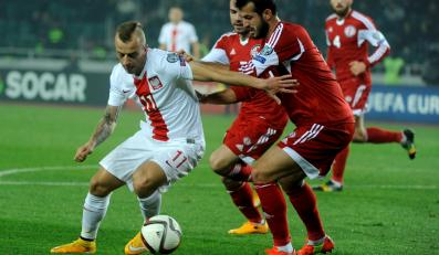 Piłkarz reprezentacji Polski Kamil Grosicki walczy o piłkę z Gia Grigalava z Gruzji w meczu eliminacji mistrzostw Europy 2016