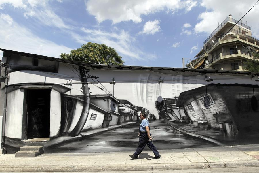 Robotnik na tle murala w Atenach