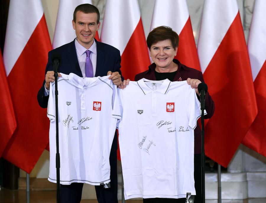 Premier Beata Szydło (P) i minister sportu i turystyki Witold Bańka (L) pozują do zdjęcia z pamiątkowymi kuszulkami podczas spotkania z medalistami mistrzostw Europy w pływaniu na krótkim basenie