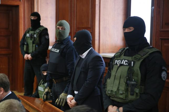 Kelner Łukasz N., chroniony przez uzbrojonych antyterrorystów i w kamizelce kuloodpornej, zasiada na ławie oskarżonych w Sądzie Okręgowym w Warszawie