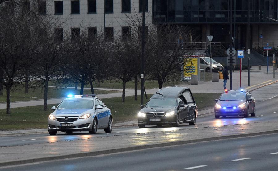 Karawan z ekshumowanym ciałem, w asyście wozów policyjnych wyjeżdża z Powązek Wojskowych